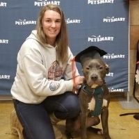 Ashley Kelleher posing with a pitbull that is wearing a graduation cap at his training school graduation.
