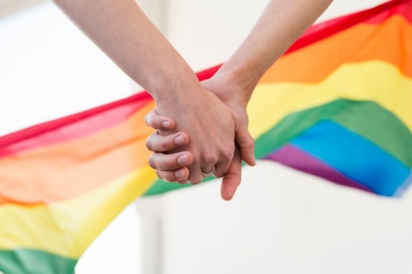 Same sex couple holding hands with a rainbow flag in the distance.